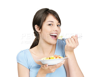 Buy stock photo Portrait of a young casual female enjoying a bowl of fresh fruits isolated against white