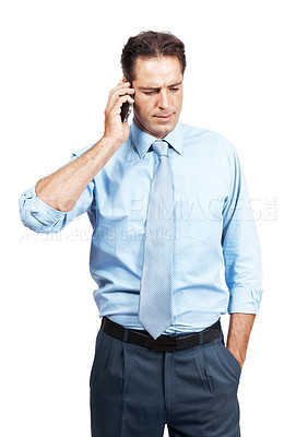 Buy stock photo A serious businessman talking on his mobile phone against a white background