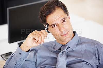 Buy stock photo Portrait of a businessman sitting at his office desk thinking with a pen in hand