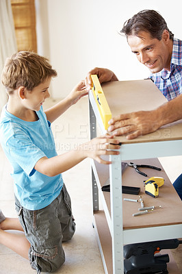 Buy stock photo Portrait of mature father teaching his little son how to check leve with spiritlevel in workshop