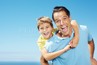 Buy stock photo Portrait of smiling father giving his son piggyback ride outdoors against sky