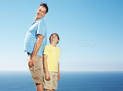 Buy stock photo Potrait of a father and son standing back to back outdoors against sky