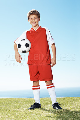 Buy stock photo Portrait of cute young football player holding soccer ball in hand standing on grass by the sea