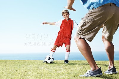 Buy stock photo Small kid playing football with his father on the field by the sea
