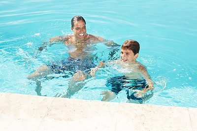 Buy stock photo Portrait of happy father and son having fun in a swimming pool on a summer day