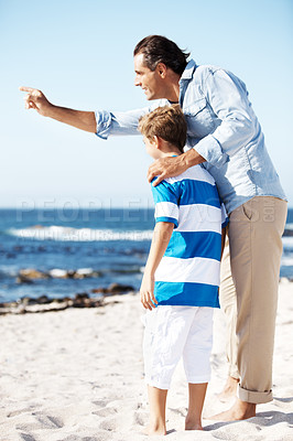 Buy stock photo Little boy with his father at the beach showing him something interesting towards the sea