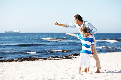 Buy stock photo Portrait of father and son both pointing towards something interesting at the sea - Copyspace