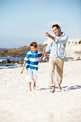 Buy stock photo Happy father walking with his son at the beach and showing him something interesting