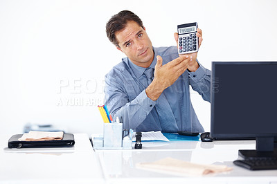 Buy stock photo Portrait of disappointed busines man sitting at his desk and showing low sales figures on the calculator