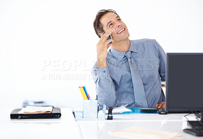 Buy stock photo Successful business man sitting at his desk and talking on mobile phone looking away