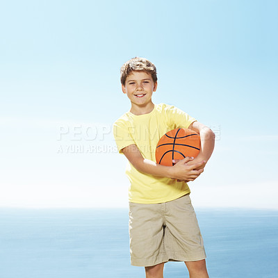 Buy stock photo Portrait of adorable small kid holding a basketball in hand while standing outside against sky