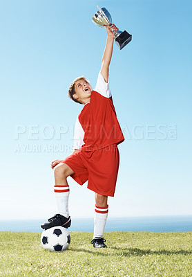 Buy stock photo Portrait of a happy young boy  holding his winning trophy with football under his feet - Outdoor