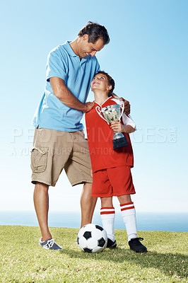 Buy stock photo Portrait of a happy mature father with his son holding a winners trophy - Outdoor