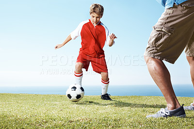 Buy stock photo Portrait of a small boy playing a soccer game with his father on a sunny day