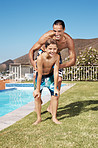 Joyful man playing with his small son by the swimming pool