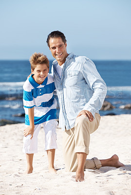 Buy stock photo Portrait of a happy mature father and his small son posing together at the beach