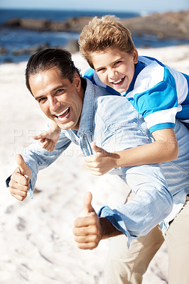 Buy stock photo Portrait of a happy father giving his son piggyback ride and gesturing thums up sign at the beach