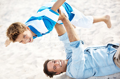 Buy stock photo Strong father lying down and holding his smiling son in the air at the beach