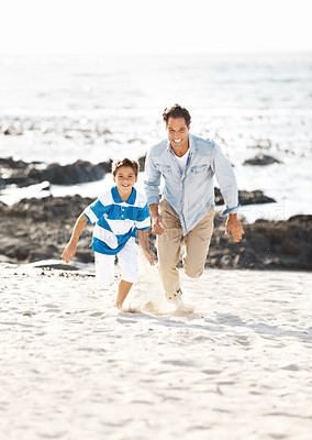 Buy stock photo Excited father and son holding ahds and running on a sandy beach - Summer holidays