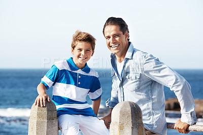 Buy stock photo Handsome father smiling with his cute son sitting on a railing by the beach