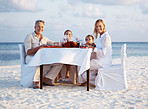 Happy family enjoying dinner at the beach