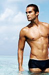 Young sexy muscular man standing in sea