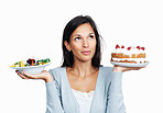 Woman thinking while holding cake and salad