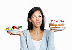 Beautiful woman thinking while holding cake and salad