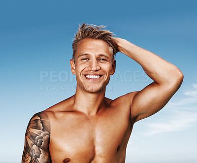 Buy stock photo Smiling young man standing against sky with hand behind head