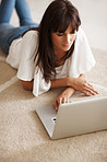 Female lying on the floor working on a laptop