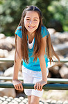 An innocent little girl on a wooden bridge smiling