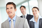 Smiling business man with his associates looking at something