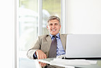 Happy mature business man with laptop at office