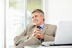Relaxed mature business male with laptop looking away