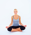 Smiling young girl sitting in lotus position on isolated blue