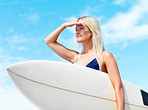 Happy young woman holding a surfboard and shielding eyes