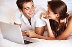 Young couple lying together at home with laptop