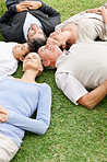 Relaxed family of five lying on grass in park