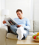 Man relaxing on couch at home reading newspaper