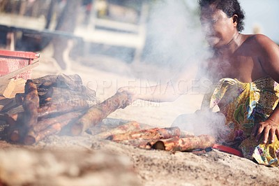 Buy stock photo A lone Thai woman is partially hidden by the smoke from a woodfire she is tending