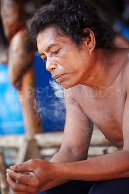 Buy stock photo Portrait of a Thai man exhaling smoke while gazing downwards thoughtfully