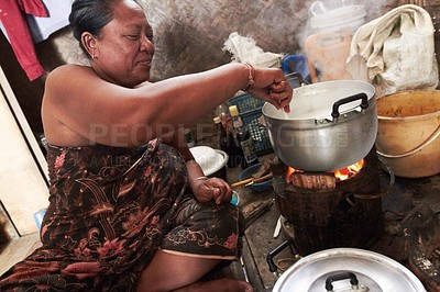 Buy stock photo A native woman stirring the food she is cooking over the fire