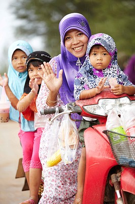 Buy stock photo A happy Thai mother waving while sitting on a scooter with her daughters