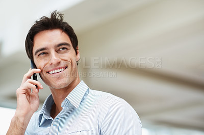 Buy stock photo Handsome man smiling while speaking on cellphone and looking at copyspace