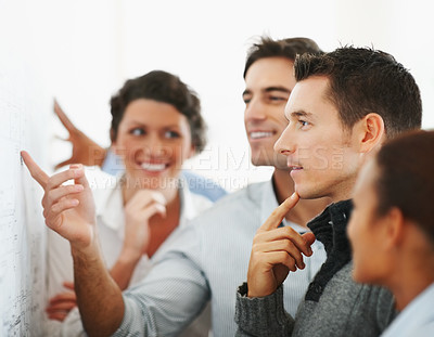 Buy stock photo Team of business colleagues looking at a chart put on the wall