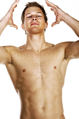 Buy stock photo Studio portrait of a bare-chested male model with his hands raised to his head isolated on white