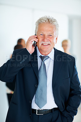 Buy stock photo Portrait of senior business man talking on cellphone with colleagues in background