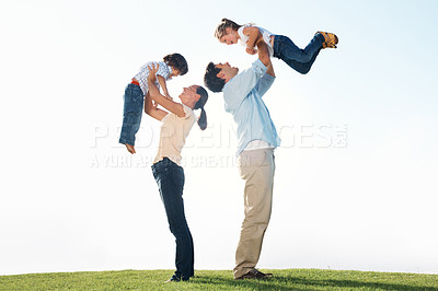 Buy stock photo Side view of middle aged parents carrying children on grass during weekend
