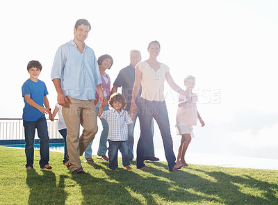 Buy stock photo Three generation family walking while holding hands on grass