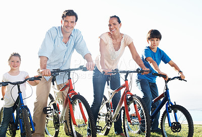 Buy stock photo Happy middle aged couple with children riding bikes in park
